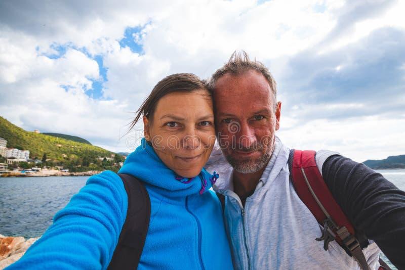 Pares felizes que tomam o selfie no fundo da cidade de Kas da baía imagem de stock royalty free