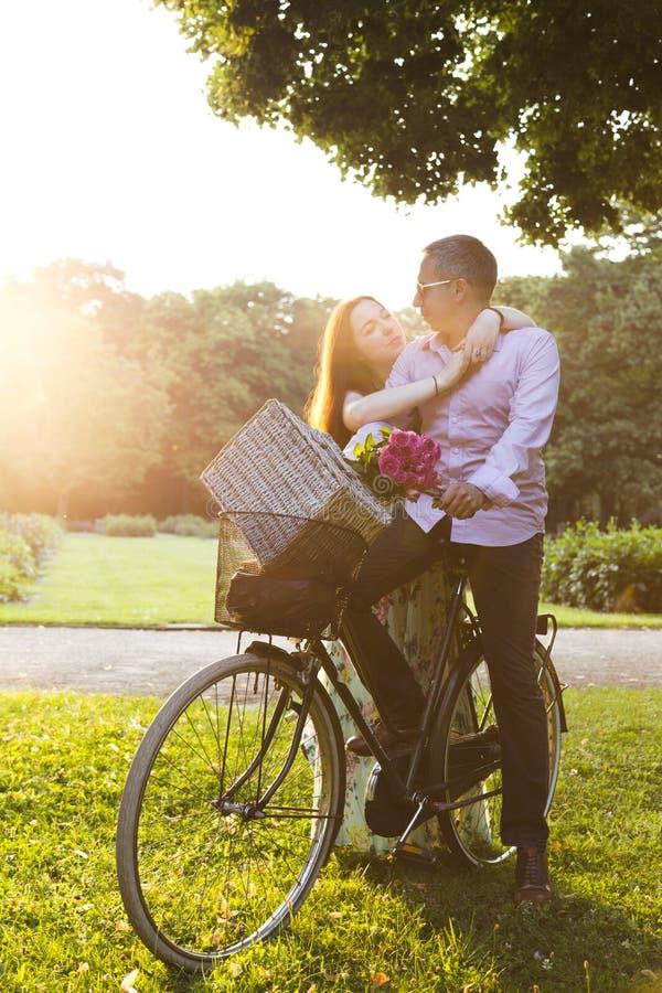 Pares felizes que vão no piquenique pela bicicleta no dia ensolarado imagens de stock