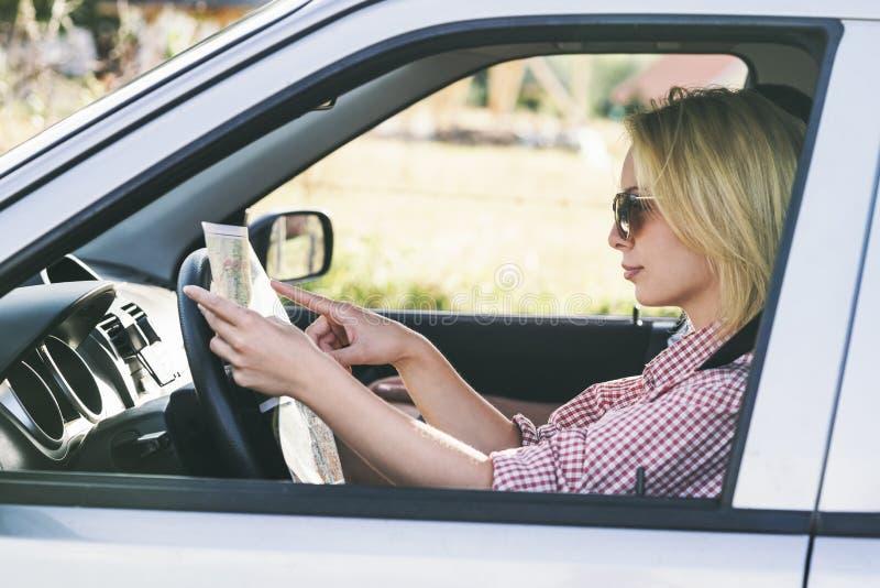 Pares felizes que viajam pelo carro na natureza e que olham no mapa Viajantes despreocupados do amigo na viagem do roadtrip do ca foto de stock royalty free