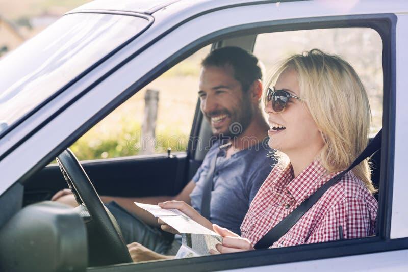 Pares felizes que viajam pelo carro na natureza e que olham no mapa Viajantes despreocupados do amigo na viagem do roadtrip do ca foto de stock