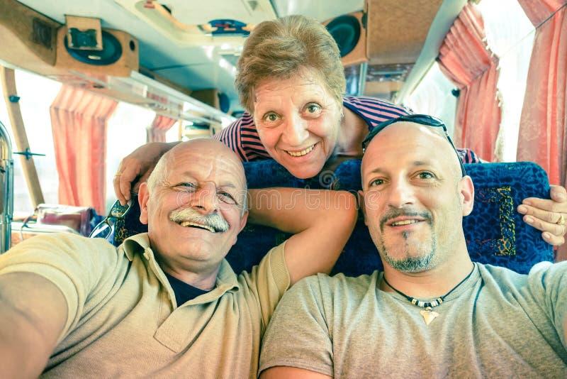 Pares felizes superiores com o filho que toma um selfie durante uma viagem do ônibus imagens de stock royalty free
