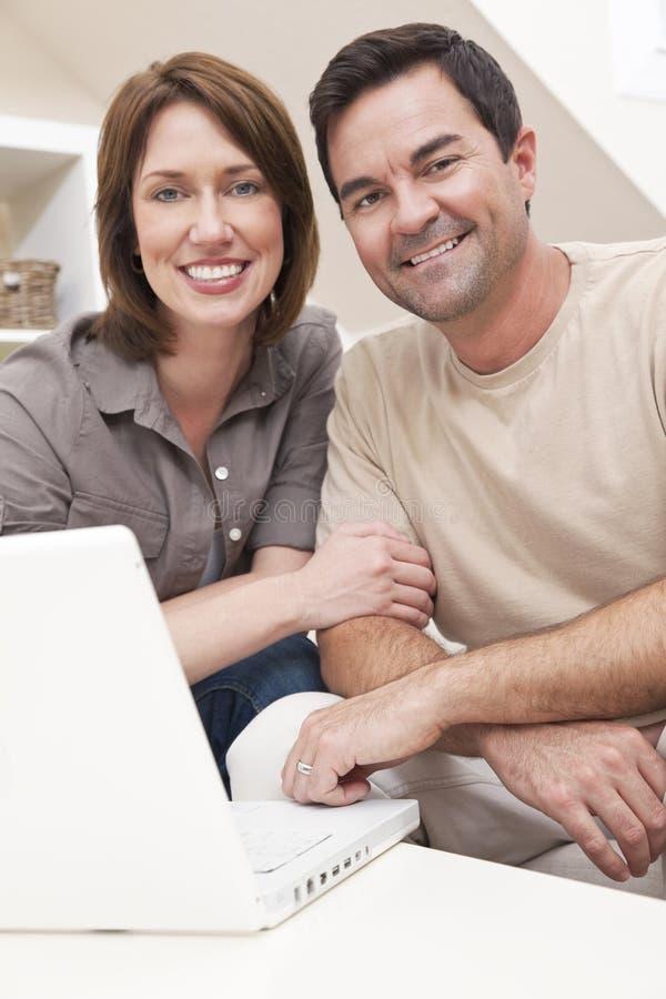 Pares felizes usando o computador portátil em casa fotografia de stock royalty free