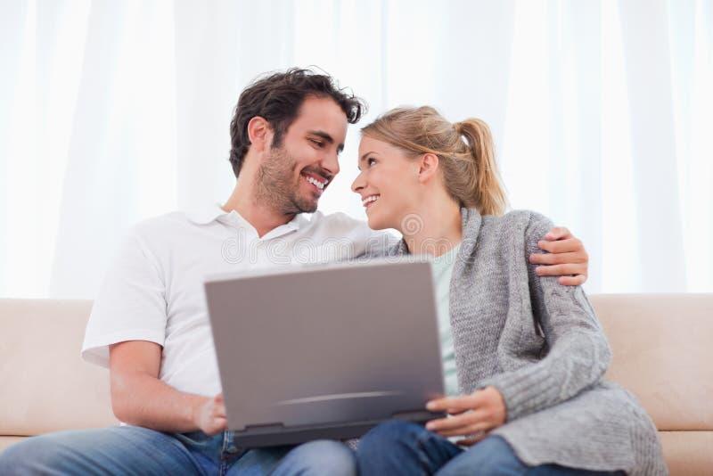 Pares felizes usando um portátil imagem de stock royalty free