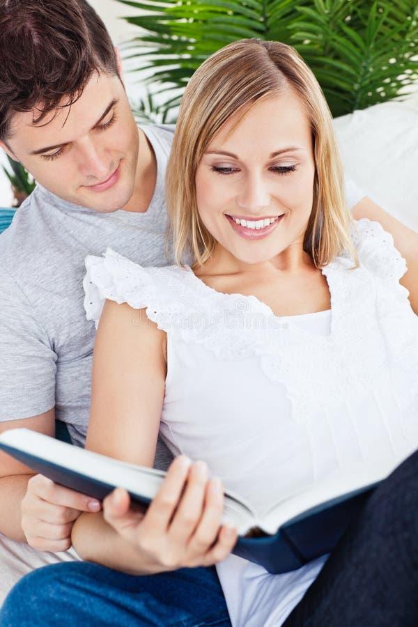 Pares focalizados que lêem um livro junto no sofá imagens de stock royalty free