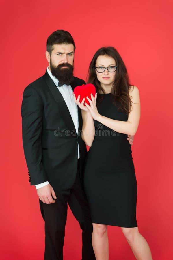 Pares formales con el corazón rojo de la tarjeta del día de San Valentín Tome mi coraz?n Un coraz?n para dos mujer atractiva y ho imagen de archivo libre de regalías