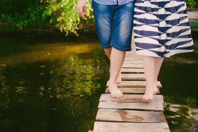 Pares frescos elegantes em uma ponte perto da água, relacionamentos, romance, pés, estilo de vida - conceito fotos de stock