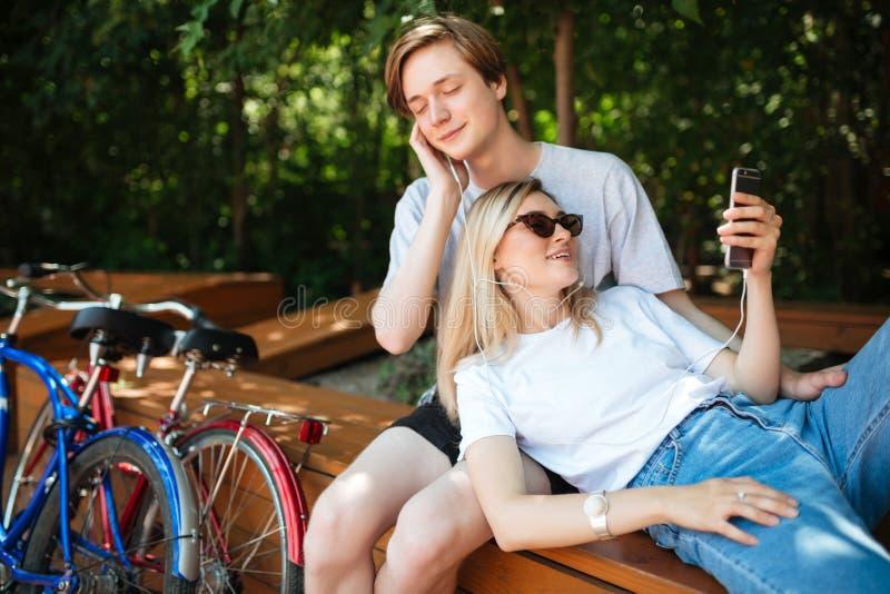 Pares frescos jovenes en música que escucha de los auriculares en parque con dos bicicletas cerca Muchacho que se sienta en banco foto de archivo