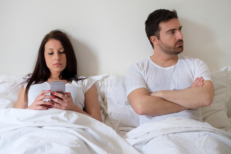 Pares furados e homem preocupado por seu apego do Internet da esposa imagens de stock