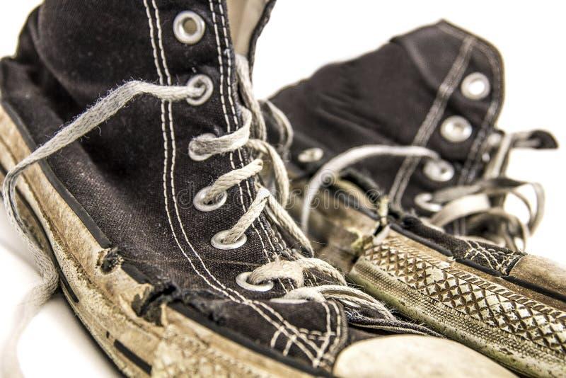 Pares gastados velhos de sapatas de tênis superiores altas preto e branco no fundo branco imagens de stock royalty free