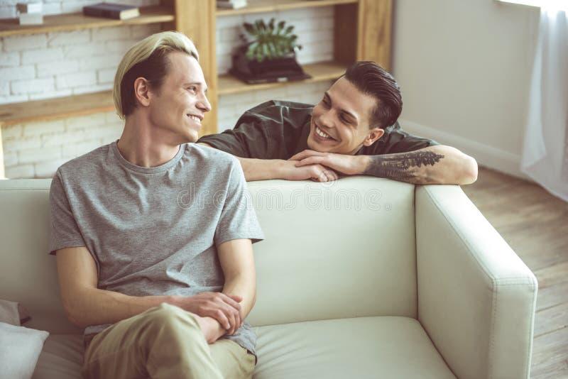 Pares gay cariñosos que miran uno a con sonrisas felices foto de archivo