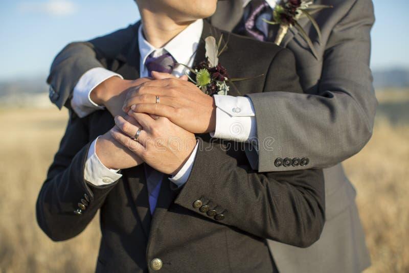 Pares gay de la boda que abrazan afuera fotografía de archivo libre de regalías
