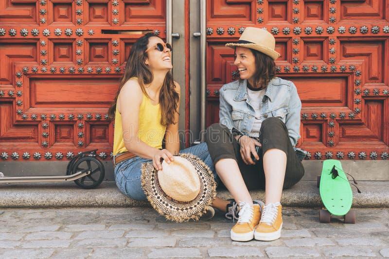 Pares gay de las mujeres jovenes que miran y que se sonr?en en un fondo rojo de la puerta La misma felicidad del sexo y concepto  fotos de archivo