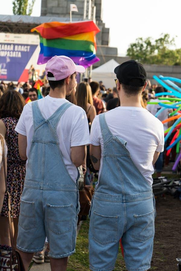 Pares gay en un concierto que disfruta del festival del orgullo en Sofía Socios homosexuales con la misma ropa y sombreros fotografía de archivo libre de regalías