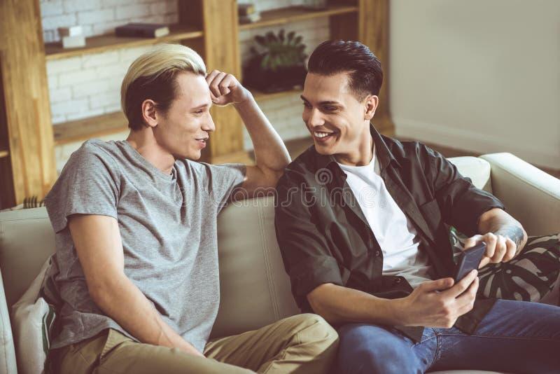 Pares gay jovenes que se sientan en un sofá y una sonrisa imágenes de archivo libres de regalías