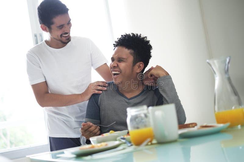Pares gay que comen el desayuno en casa por la mañana imagen de archivo