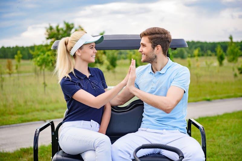 Pares golfing atrativos que dão-se olá!-cinco imagem de stock royalty free