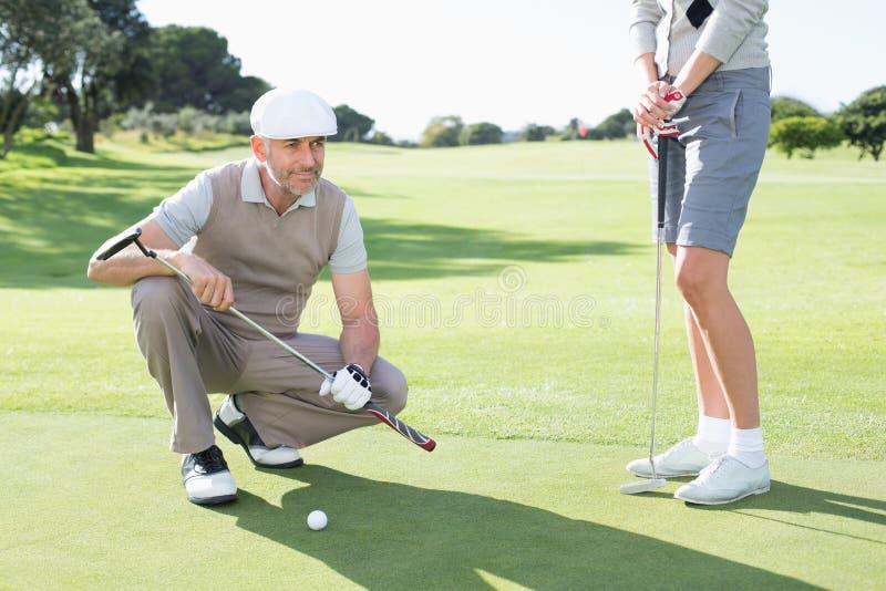 Pares Golfing en el putting green imagen de archivo libre de regalías