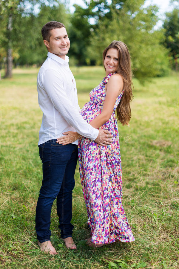 Pares grávidos bonitos felizes junto esperando uma criança Homem e mulher que andam no parque Compartilhe do amor e da família, e imagens de stock royalty free