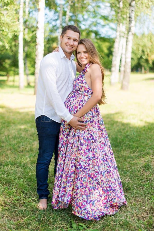 Pares grávidos bonitos felizes junto esperando uma criança Homem e mulher que andam no parque Compartilhe do amor e da família, e fotos de stock
