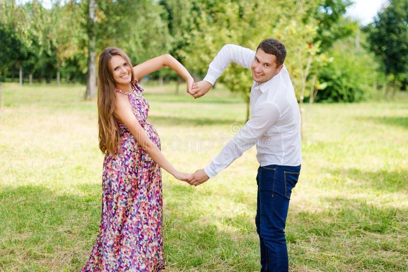 Pares grávidos bonitos felizes junto esperando uma criança Homem e mulher que andam no parque que mostra o coração com mãos Compa fotografia de stock royalty free