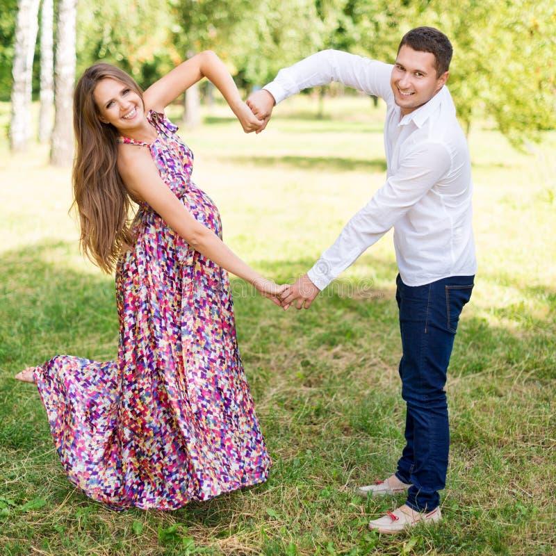 Pares grávidos bonitos felizes junto esperando uma criança Homem e mulher que andam no parque que mostra o coração com mãos Compa foto de stock