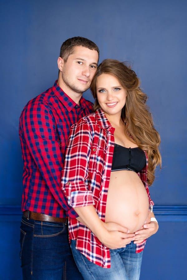 Pares grávidos bonitos felizes junto esperando uma criança Retrato do estúdio fotos de stock royalty free