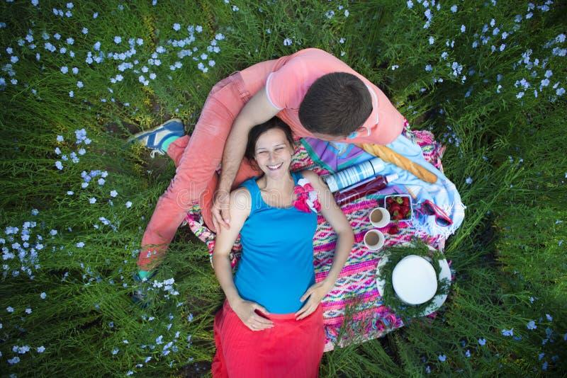 Pares grávidos bonitos felizes novos no campo de linho fotografia de stock