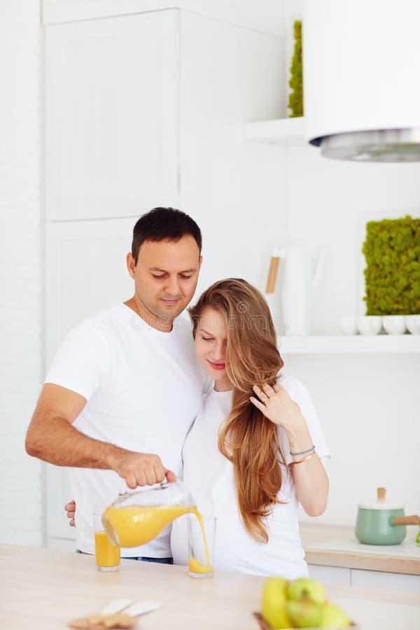 Pares grávidos de sorriso que bebem o suco fresco na cozinha na manhã fotografia de stock royalty free