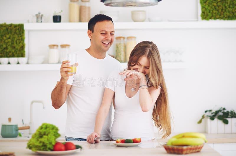 Pares grávidos dos jovens que têm o divertimento, ao preparar o café da manhã na cozinha fotos de stock