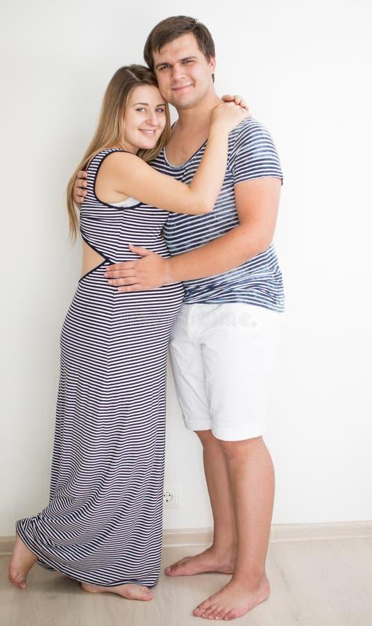 Pares grávidos em roupa listrada que levanta contra a parede branca fotografia de stock