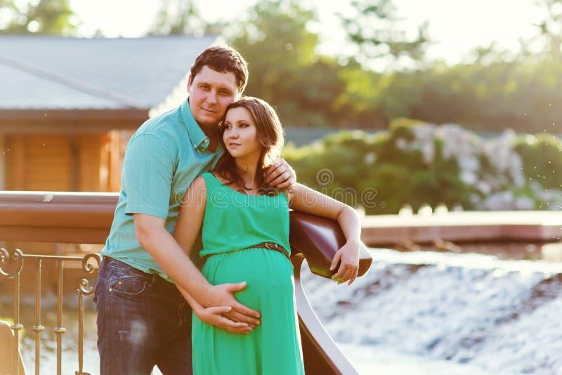 Pares grávidos felizes e dos jovens que abraçam na natureza fotos de stock