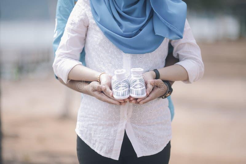 Pares grávidos felizes e dos jovens que abraçam na natureza fotos de stock royalty free