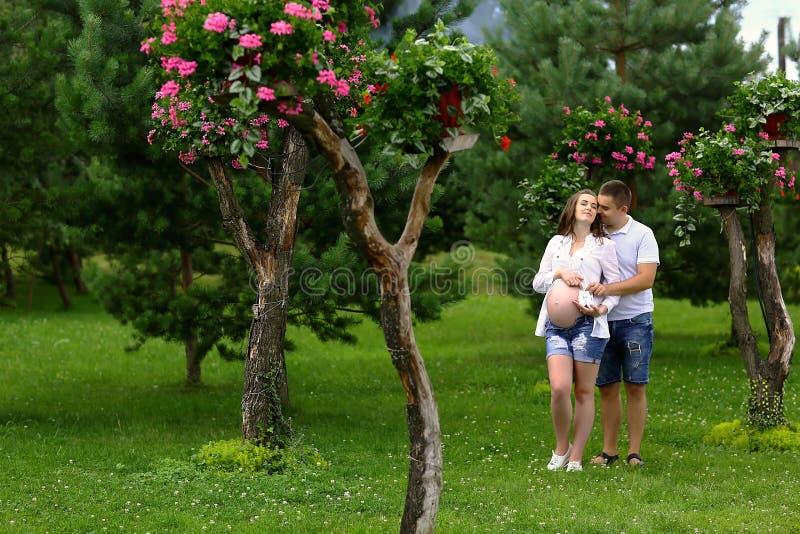 Pares grávidos felizes e dos jovens que abraçam na natureza Imagem autêntica do estilo de vida Lugar para o texto fotos de stock