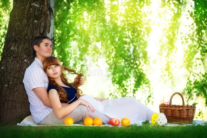Pares grávidos felizes e dos jovens que abraçam na natureza que aprecia o summe imagens de stock royalty free