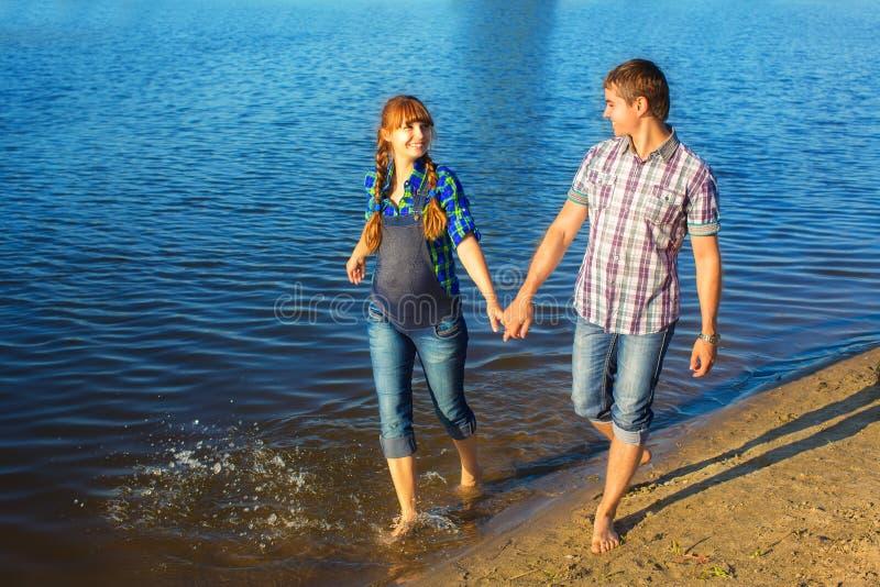 Pares grávidos felizes e dos jovens que têm o divertimento na praia verão fotos de stock