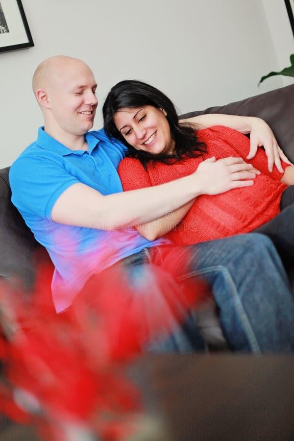 Pares grávidos felizes em casa imagem de stock