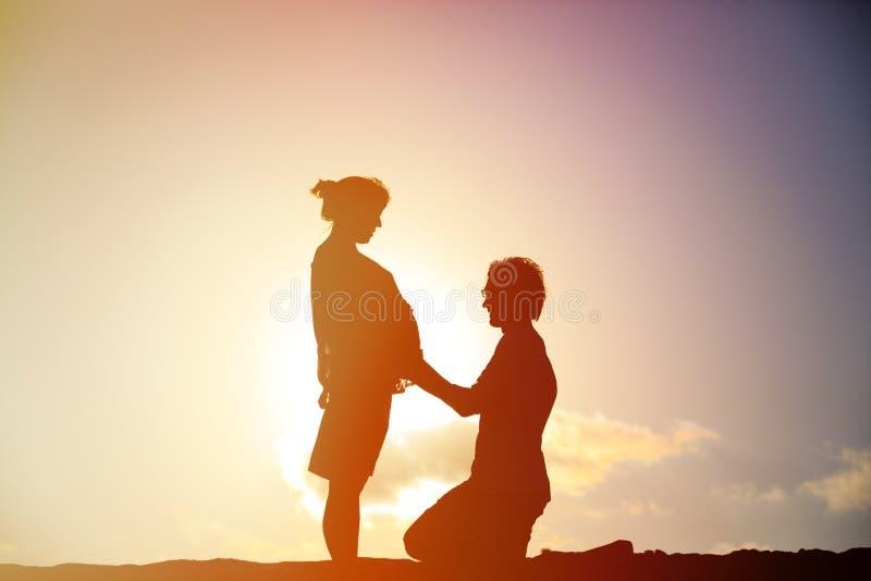 Pares grávidos felizes na praia do por do sol fotos de stock royalty free