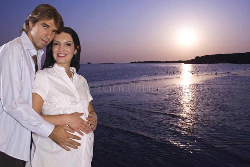 Pares grávidos felizes na praia no nascer do sol fotografia de stock royalty free
