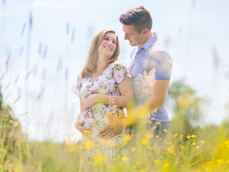 Pares grávidos felizes novos que abraçam na natureza foto de stock