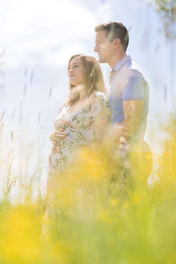 Pares grávidos felizes novos que abraçam na natureza fotos de stock