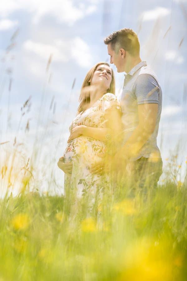 Pares grávidos felizes novos que abraçam na natureza imagens de stock royalty free