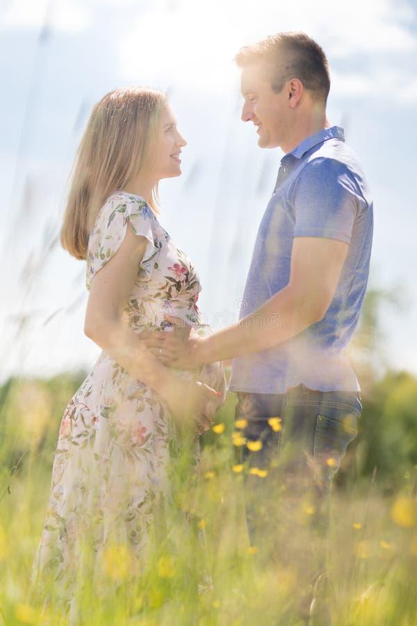 Pares grávidos felizes novos que abraçam na natureza imagem de stock