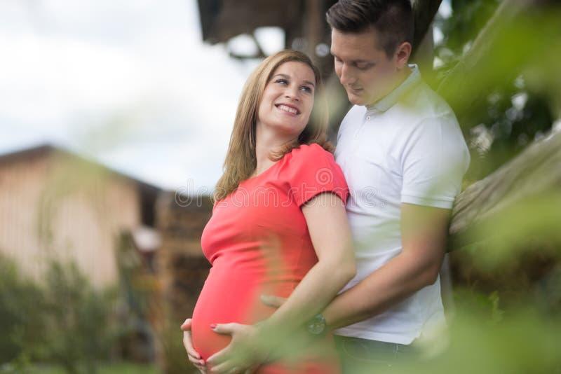 Pares grávidos felizes novos que abraçam no campo pelo hayrack fotos de stock