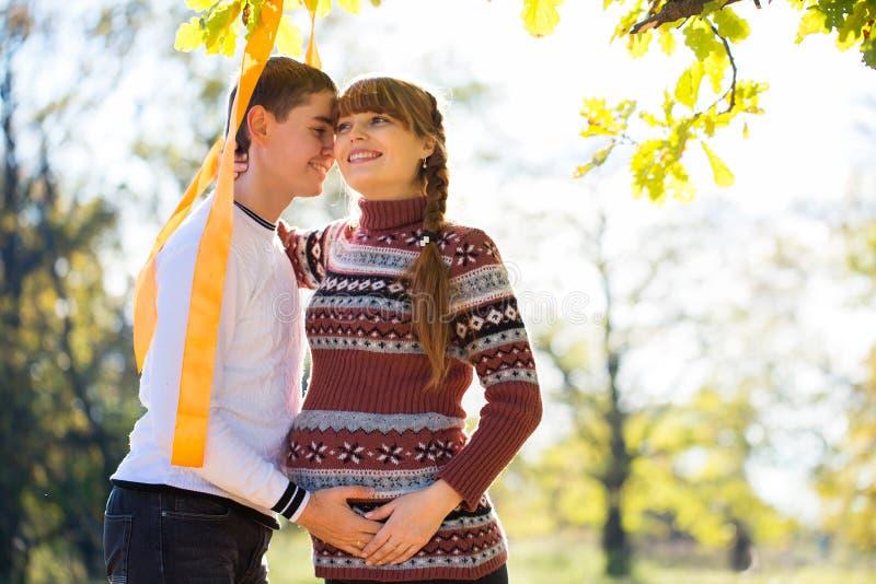 Pares grávidos novos bonitos que têm o piquenique no parque do outono Ha foto de stock