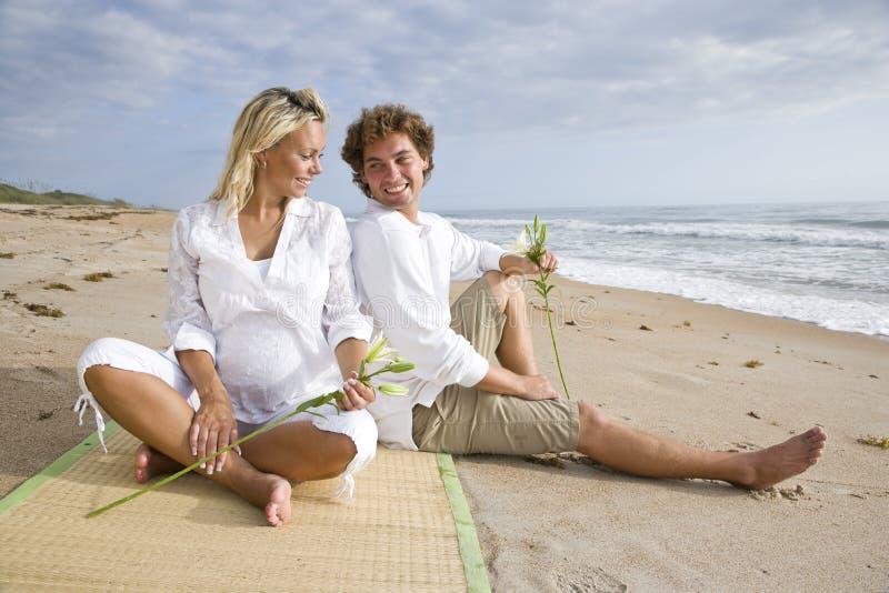 Pares grávidos novos felizes que relaxam na praia imagens de stock
