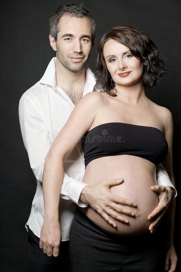 Pares grávidos que levantam no fundo escuro. imagens de stock royalty free