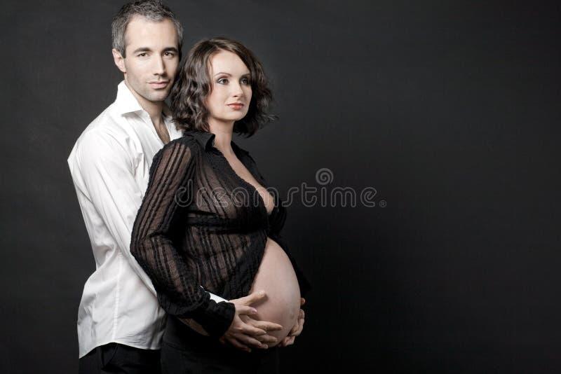 Pares grávidos que levantam no fundo escuro. fotografia de stock royalty free