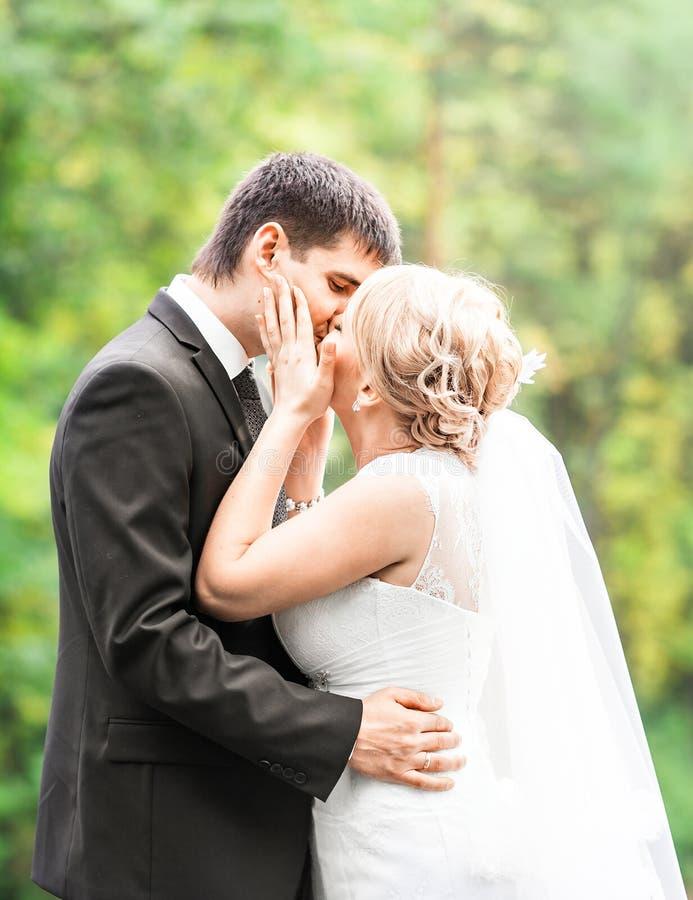 Pares hermosos de la boda al aire libre Besan y se abrazan foto de archivo