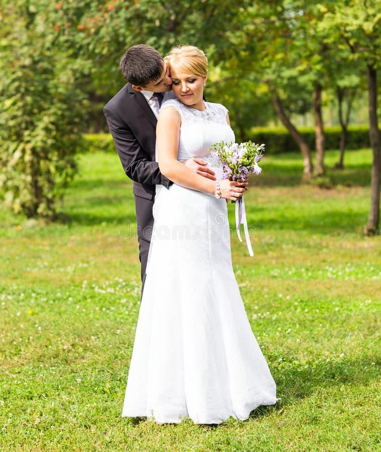 Pares hermosos de la boda al aire libre Besan y se abrazan imagen de archivo libre de regalías