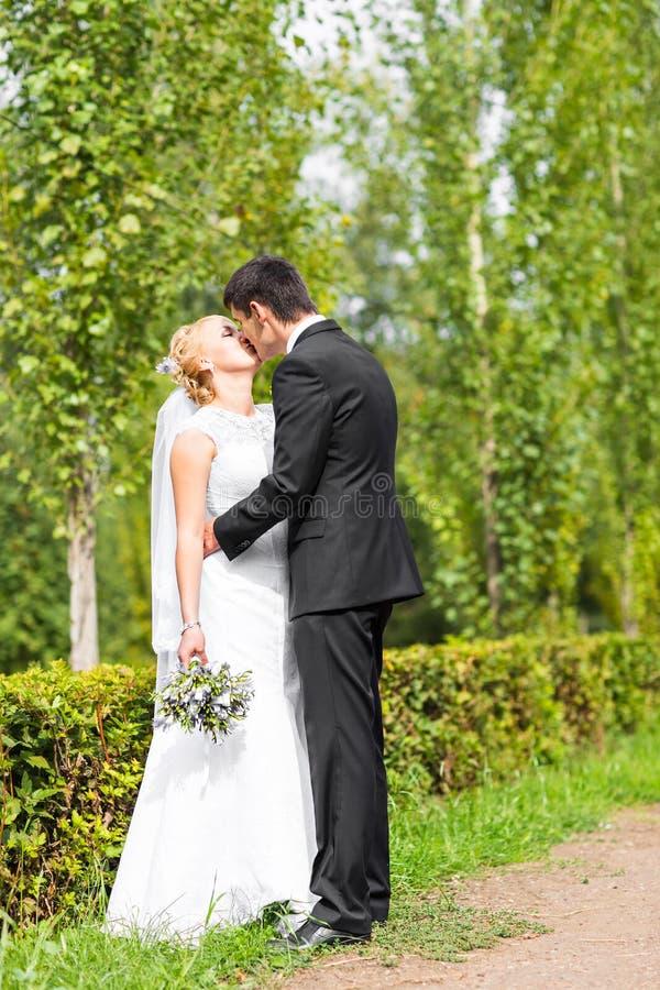 Pares hermosos de la boda al aire libre Besan y se abrazan foto de archivo libre de regalías